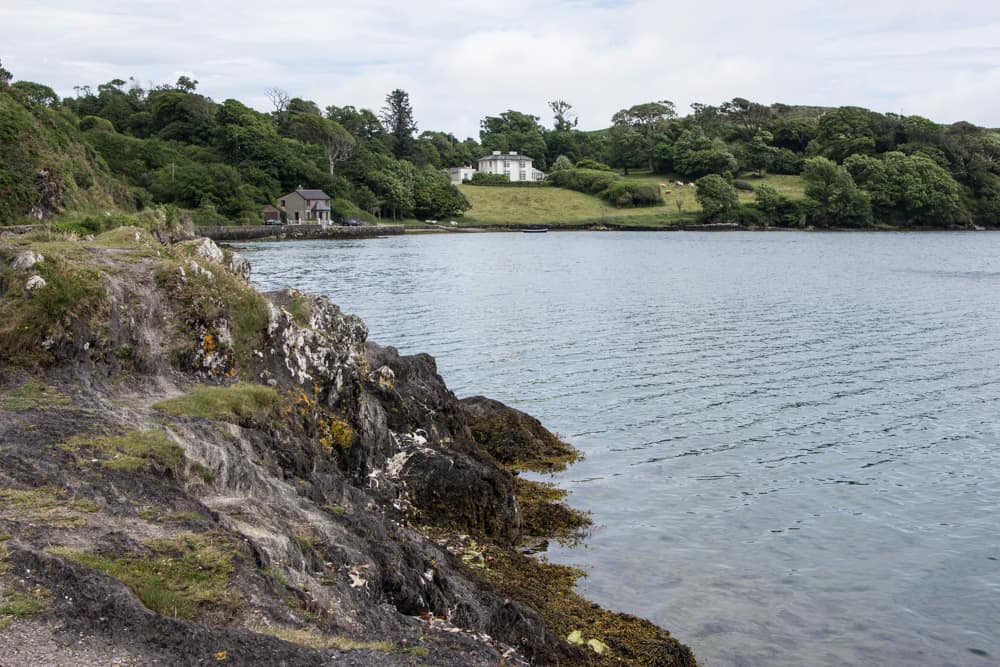 lough hyne in ireland has bright blue water and grassy hills