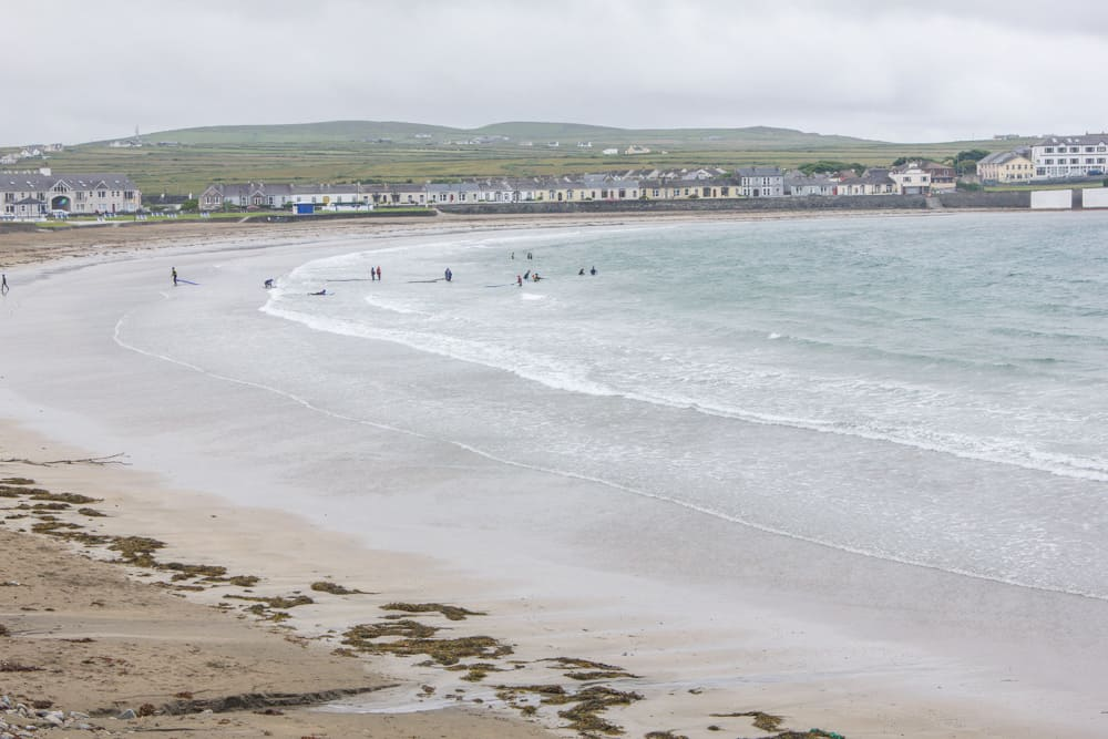 A beach in Kilkee in Ireland on a cloudy day, with surfers in the water and surrounded by grassy hills and houses - a stop on our hitchhiking journey