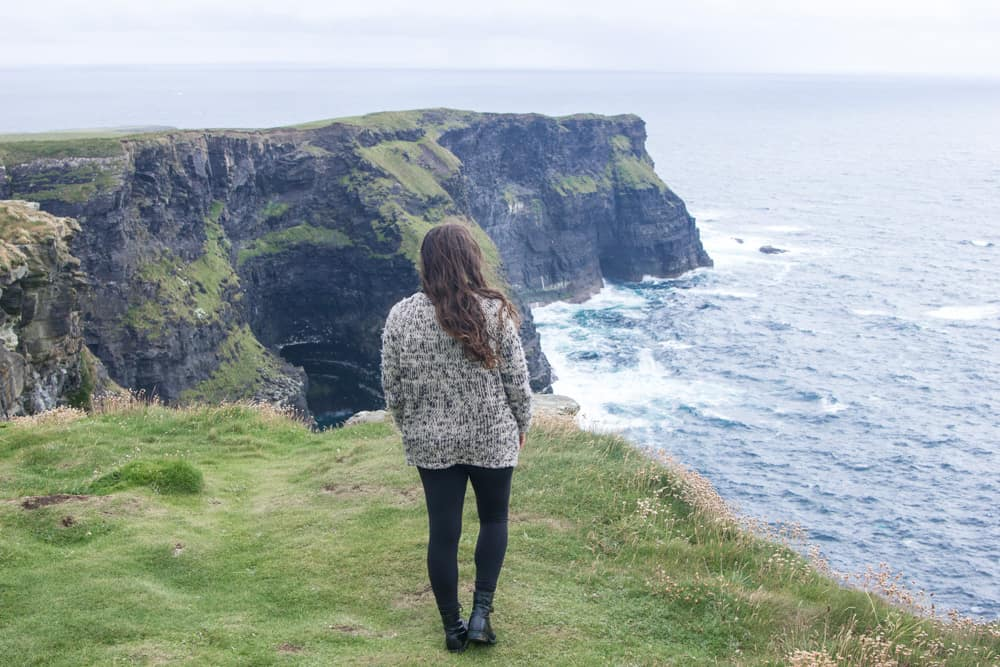 brunette girl standing on cliffs of moher in ireland overlooking ocean