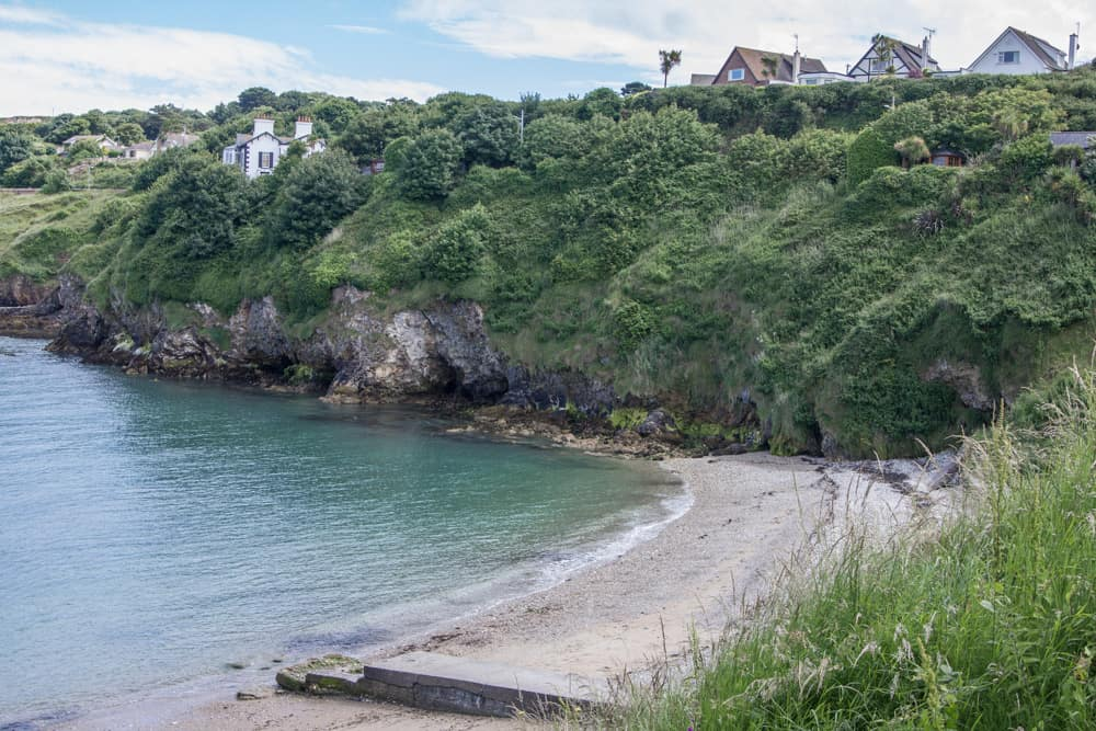 beach with bright blue water on howth cliff walk in dublin