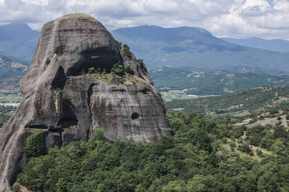 Large rock surrounded by trees at Meteora in Greece
