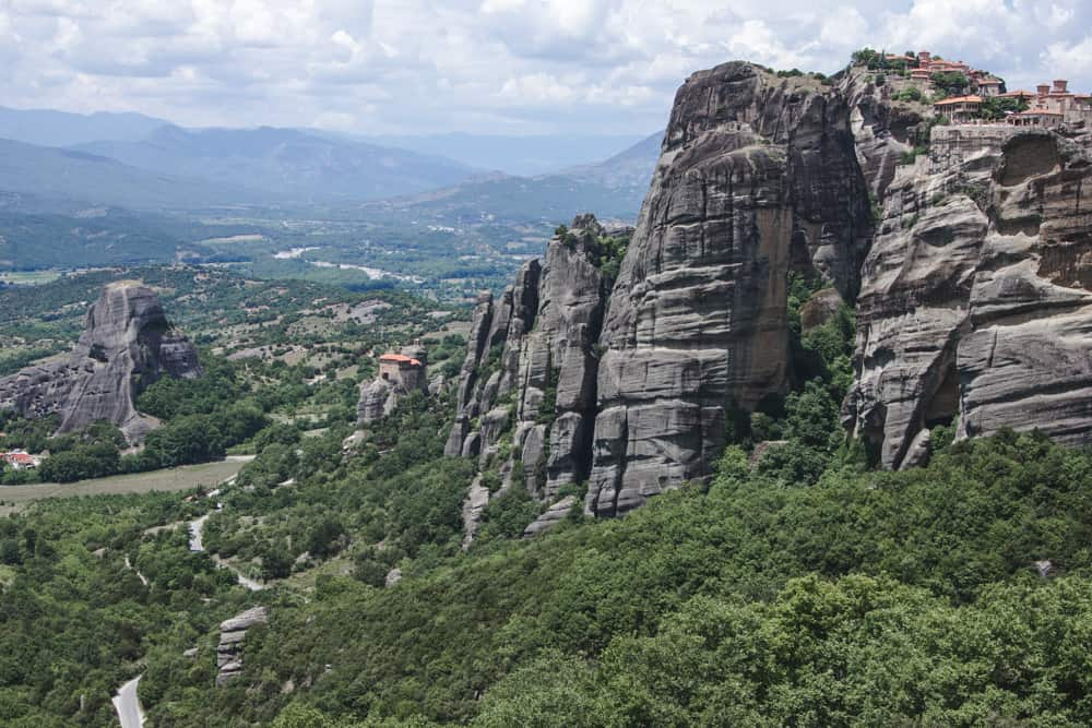 Monastery on a cliff at Meteora in Greece above trees, giant rocks, and the valley below