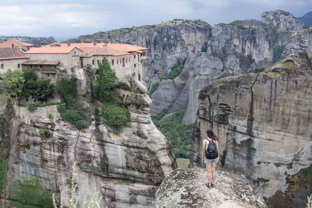 Girl looking at a Monastery on a cliff at Meteora in Greece overlooking trees and giant rocks