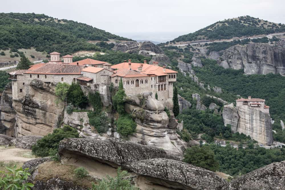 Monastery on a cliff at Meteora in Greece overlooking trees and giant rocks