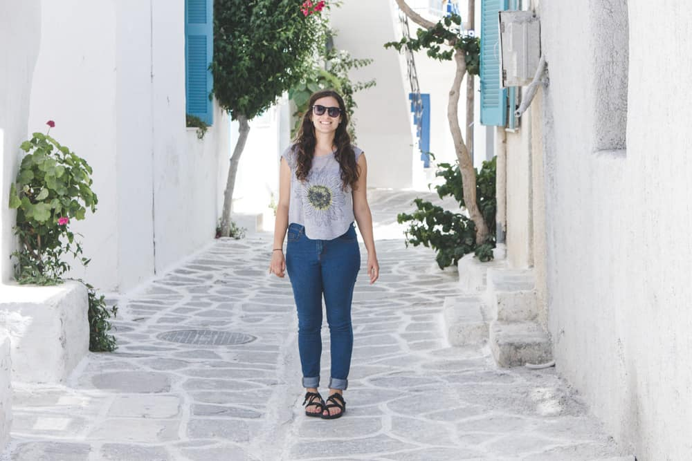 Standing on a white cobblestone street in paros in greece surrounded by white buildings with blue shutters and green plants