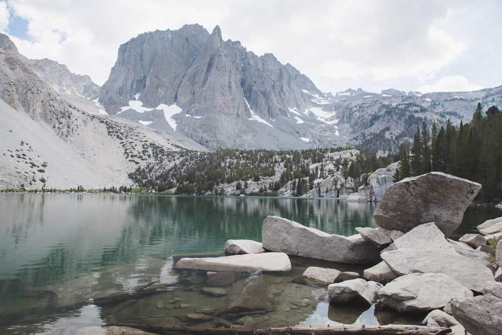 Second Lake in and Temple Crag in Big Pine Lakes near Mammoth, California is a light green lake surrounded by rocks and trees and overlooked by a large mountain
