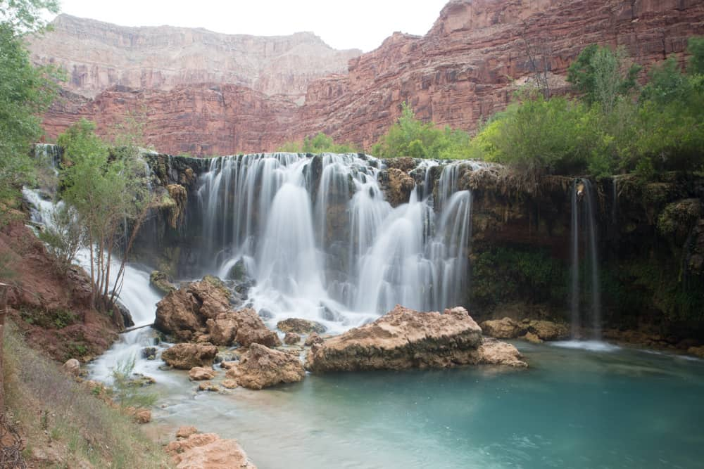 Navajo Falls in Havasupai with bright blue water and red canyon walls in the background