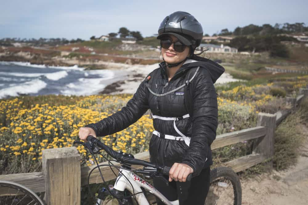 Girl on a bike on the 17-Mile Drive in Monterey in California with ocean and yellow flowers in the background