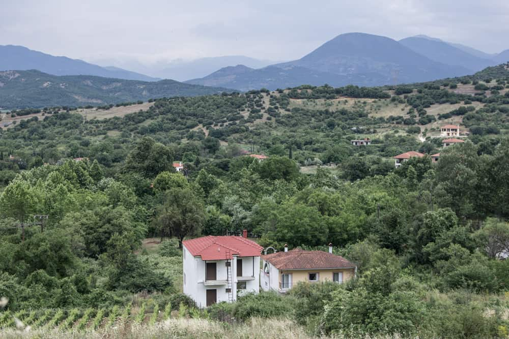 A white house with a red roof at the base of Meteora, surrounded by hills and trees