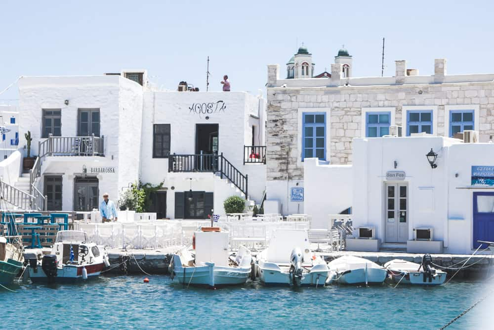 Naoussa harbor in Paros, Greece is full of blue water and white and blue buildings