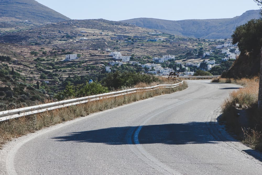 road in paros in greece surrounded by desert vegetation and white houses in June