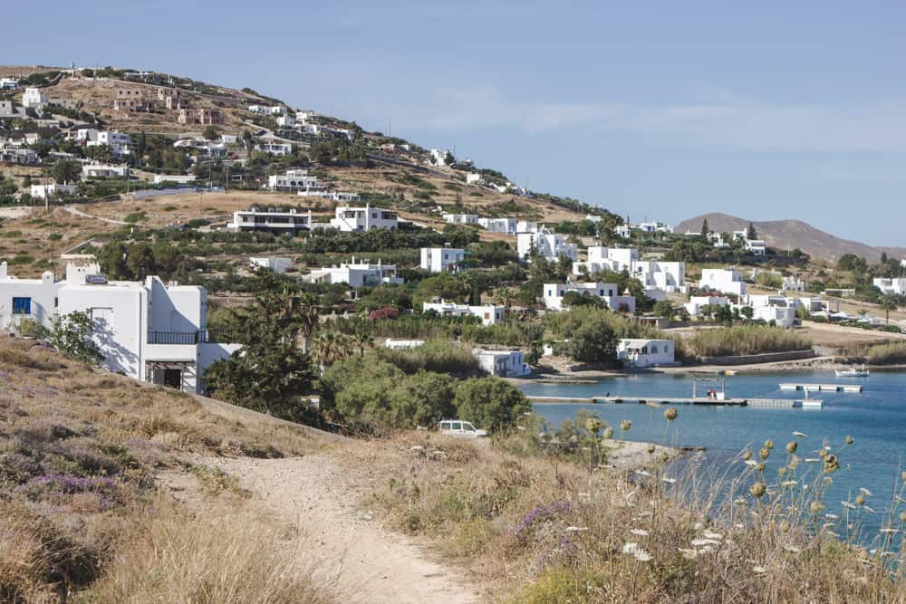 Pathway to the beach in Paros, Greece surrounded by ocean, and hills with white buildings