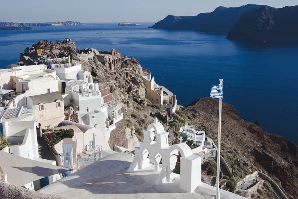 View of white houses on a cliff overlooking blue water in Santorini, Greece