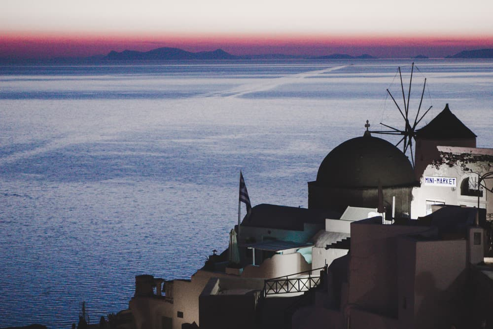 Pink sunset over the ocean in Oia in Santorini, Greece