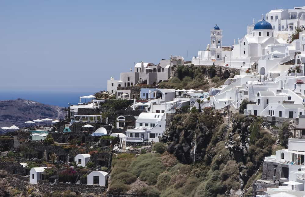 View of white buildings and blue-domed churches along the caldera in Santorini, Greece