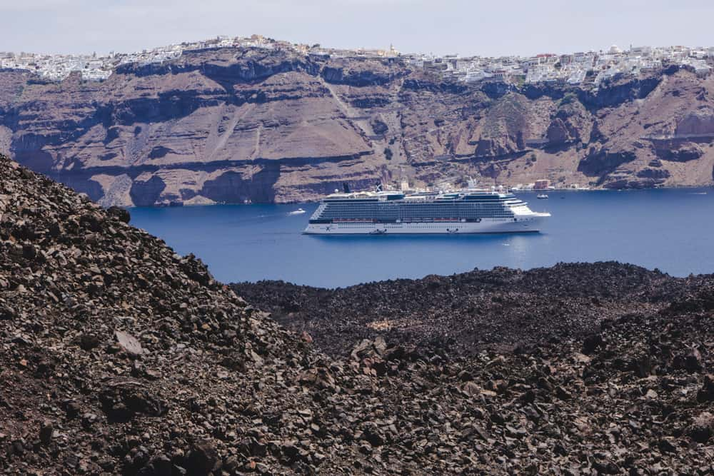 Ferry on water surrounded by cliffs in Santorini, Greece