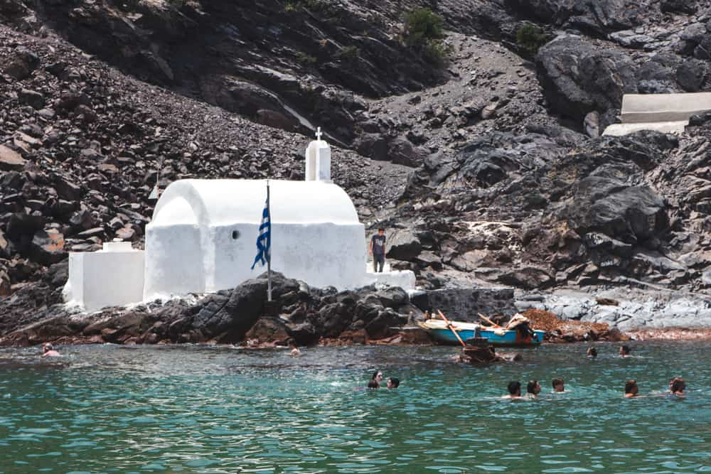 White building surrounded by green water during the volcano and hot springs tour in Santorini, Greece