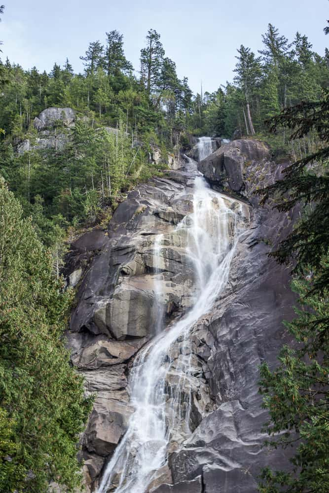 Shannon Falls is a waterfall running over a rocky mountain and surrounded by trees near Vancouver, Canada, BC