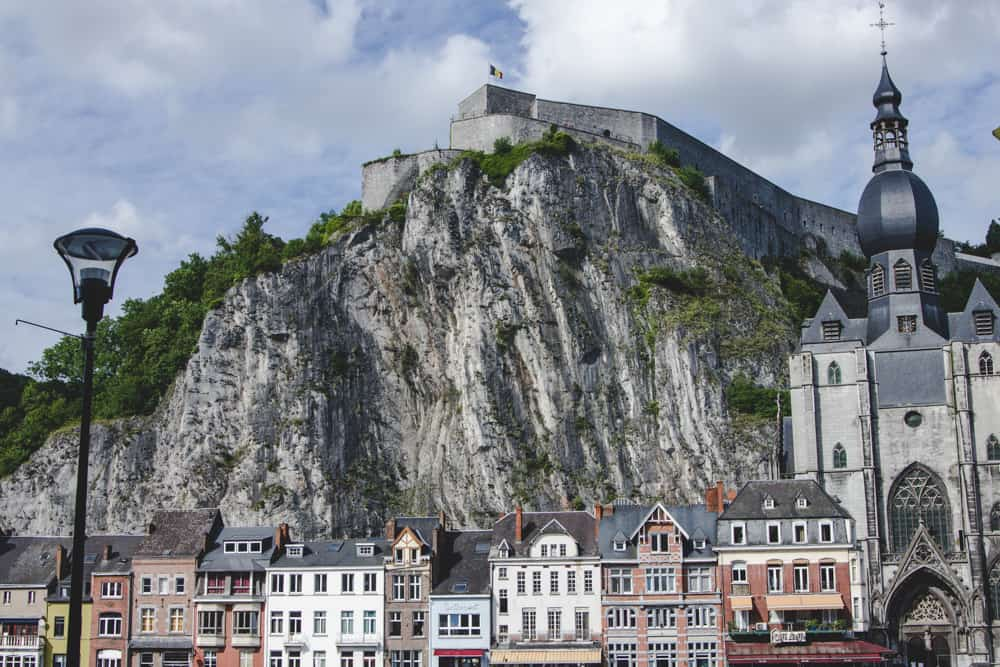 Buildings line the bottom of a large cliff with a castle perched on top in Dinant, Belgium