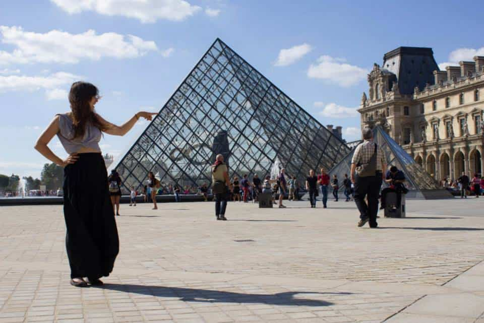 Girl pretending to poke one of the glass pyramids at the Louvre in Paris