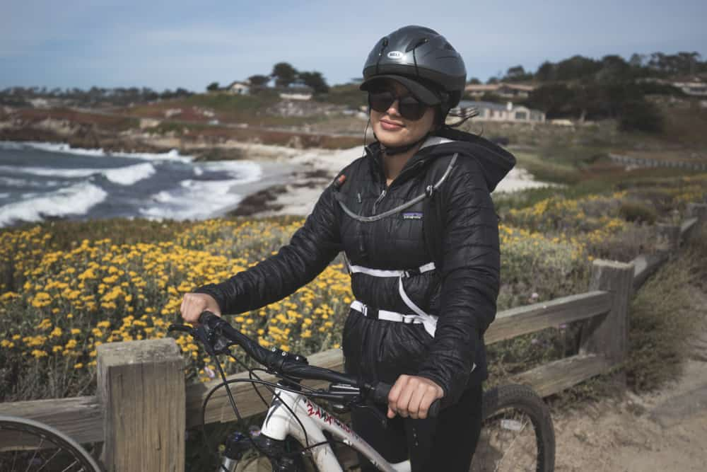 A girl on a bike with the ocean behind her on the 17-Mile Drive in Monterey, California