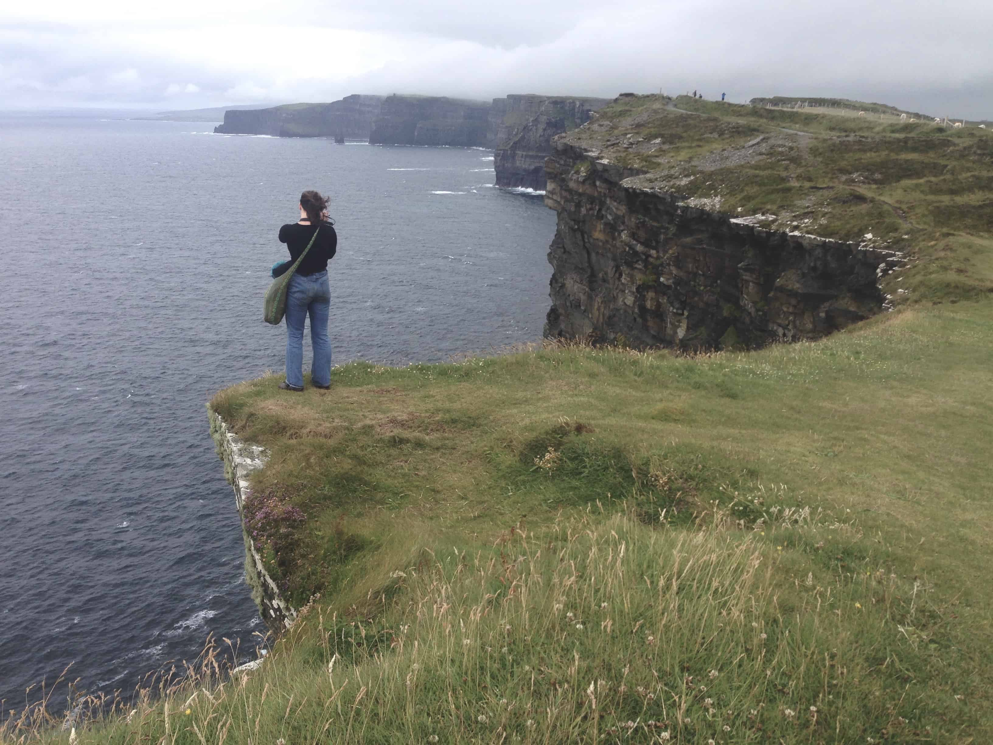 The Cliffs of Moher in Ireland are green and dramatically hover over the ocean
