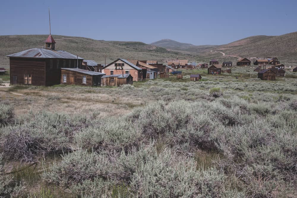 Wooden houses spread across a bunch of sage at Bodie State Historical Park in the Eastern Sierras in California