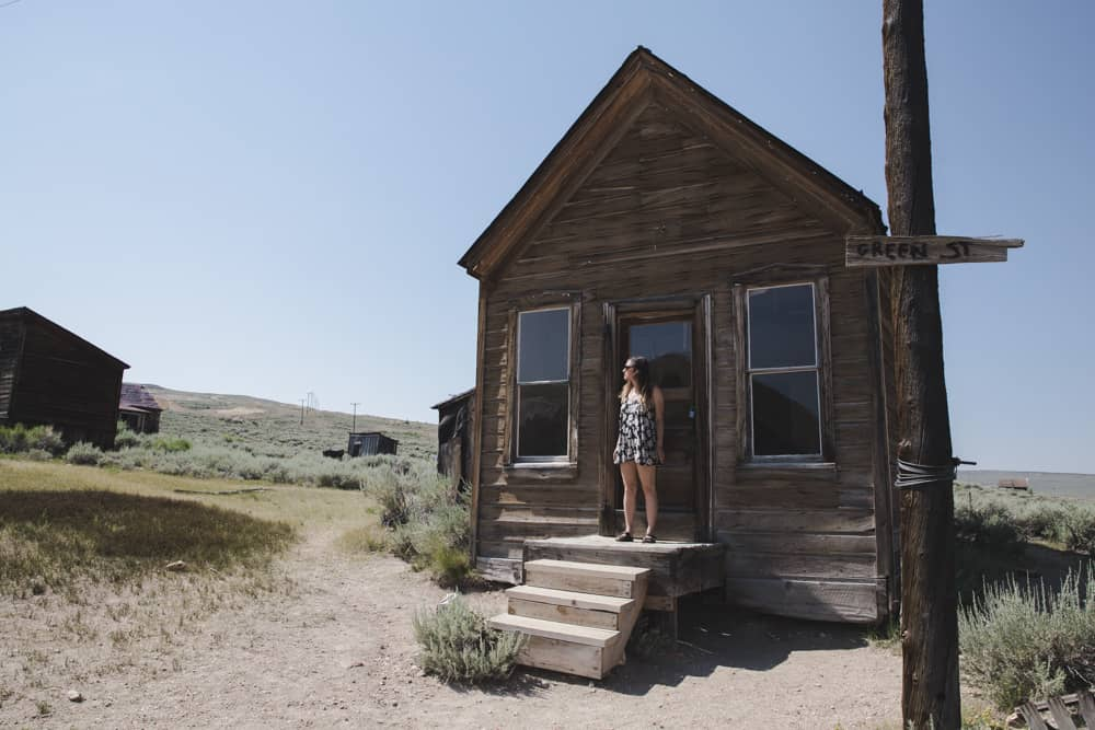 Girl standing outside an abandoned wooden building in Bodie State Historic Park in the Mammoth area in California