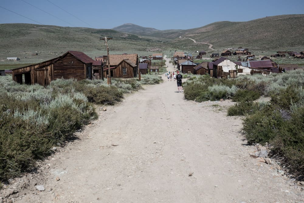 Road along Bodie, a ghost town with old wooden houses and sage bushes, in the Eastern Sierras near Mammoth in California