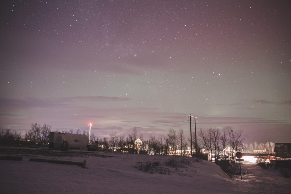Green Northern Lights over a snowy landscape in Abisko, Sweden