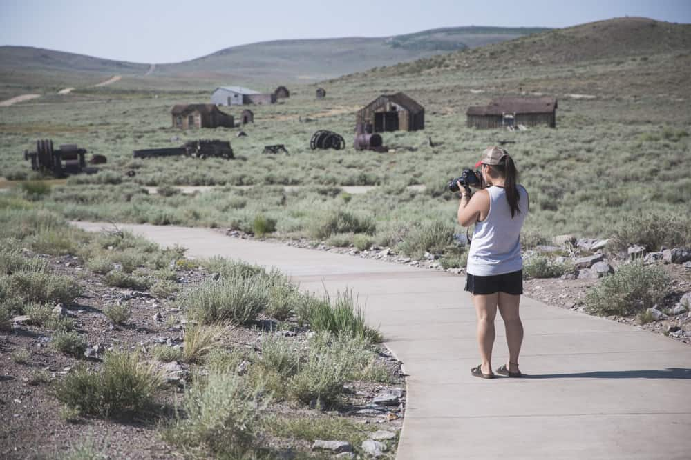 Girl taking photographs of Bodie State Historical Park, a ghost town amidst green sage bushes in the Eastern Sierras in California