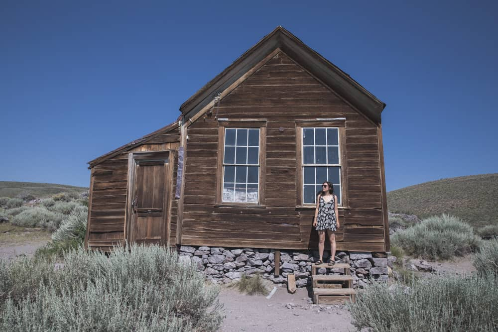 Standing in front of a wooden house at Bodie State Historical Park in the Eastern Sierras in California
