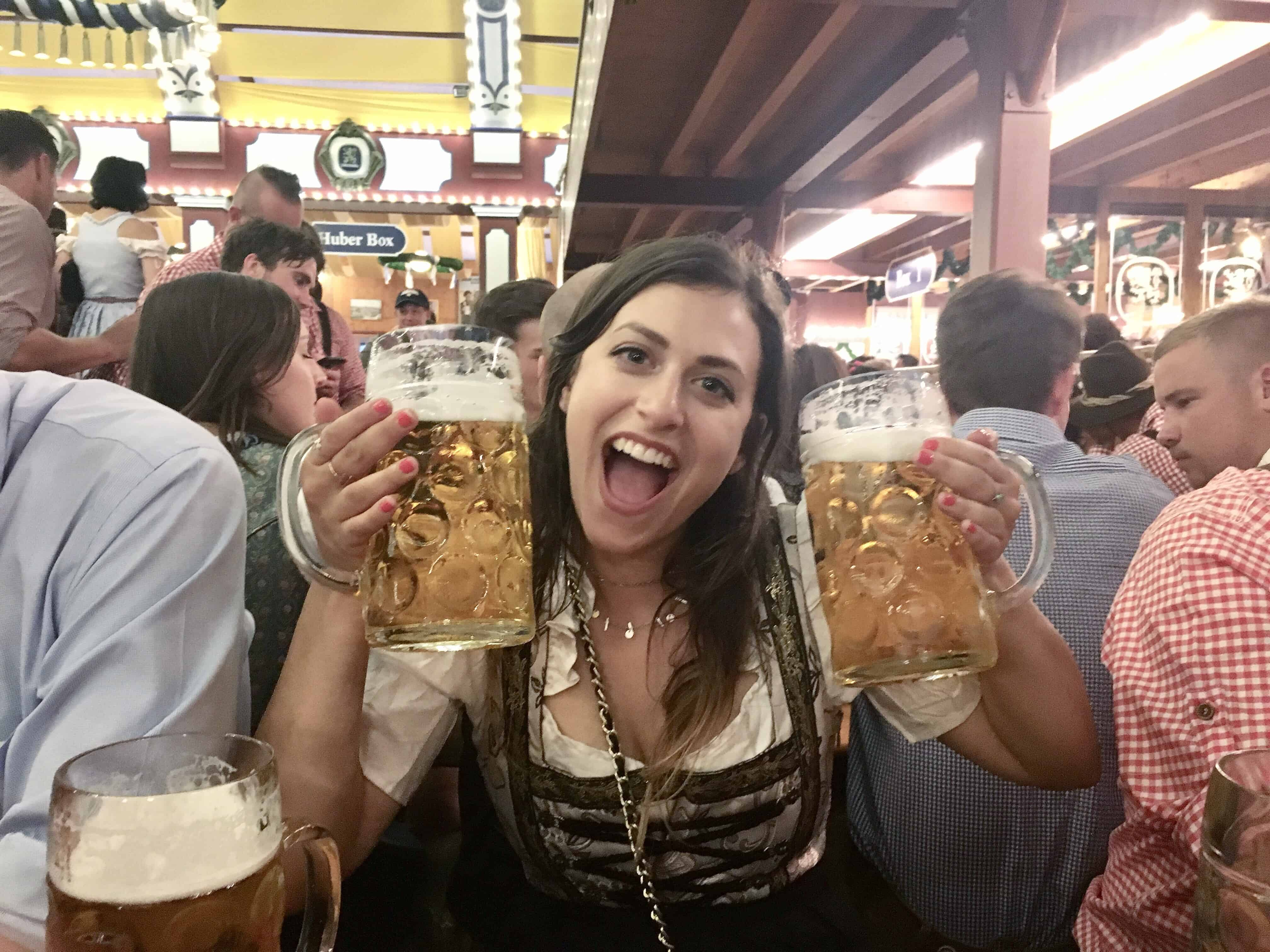 Holding two steins, or Maß, at Oktoberfest in Munich, Germany in the Löwenbräu tent