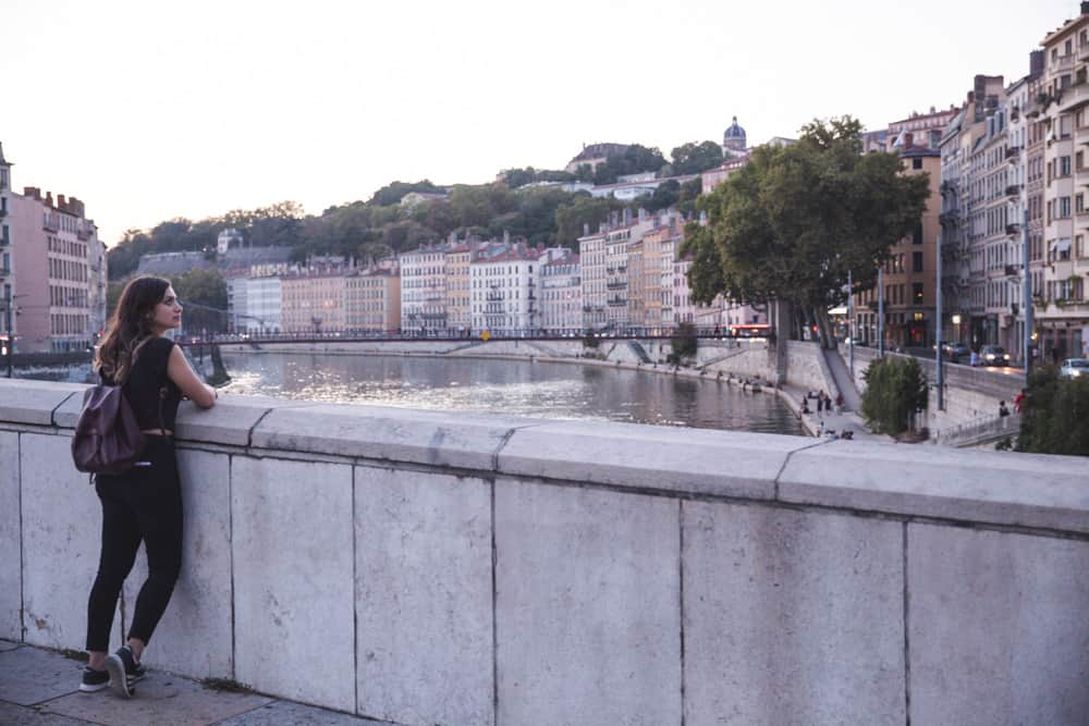 Girl looking at the view of the Saône River from a bridge in Lyon around sunset
