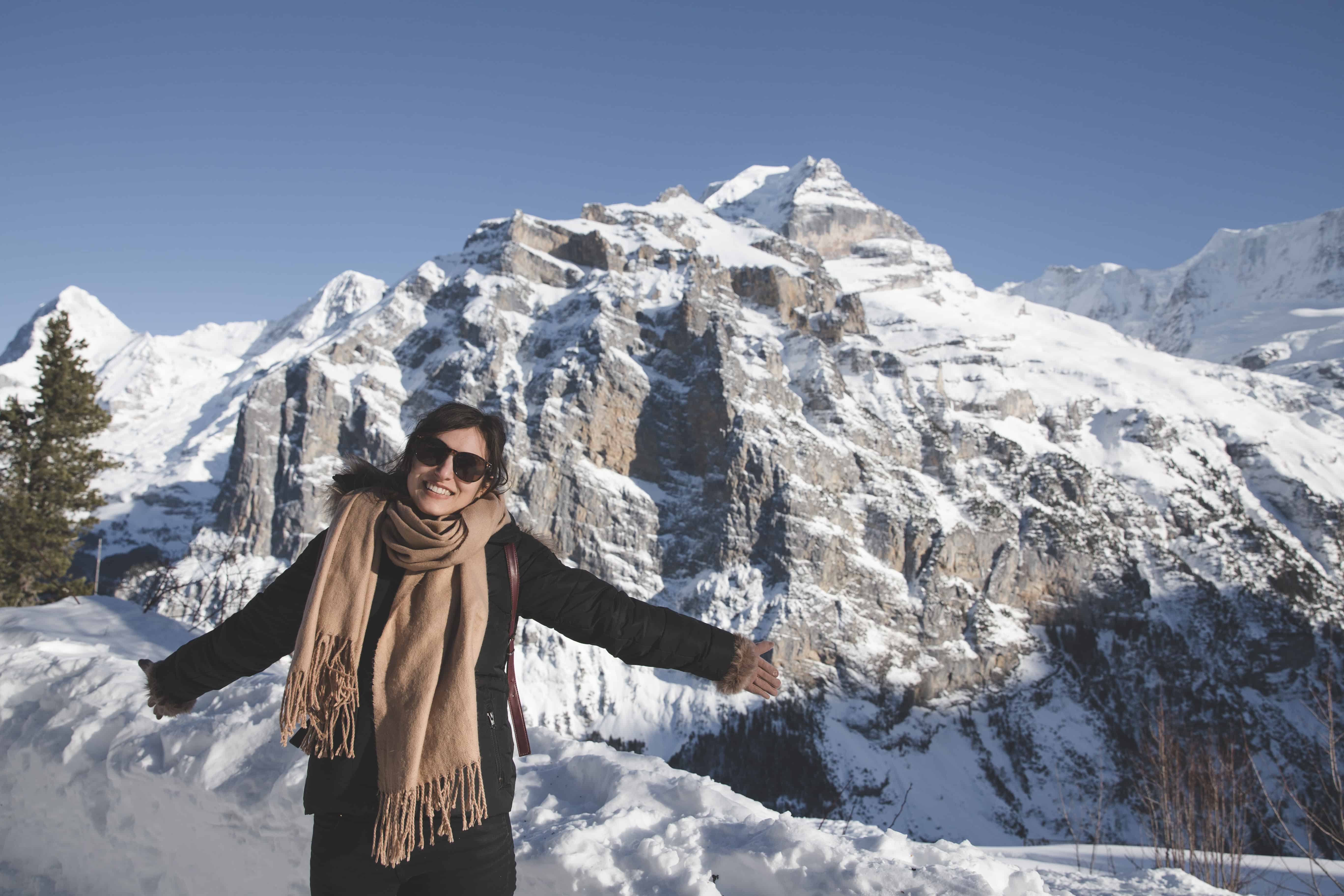 Kelsey in front of a mountain in Mürren in Switzerland on a sunny, snowy day in winter wearing winter clothes