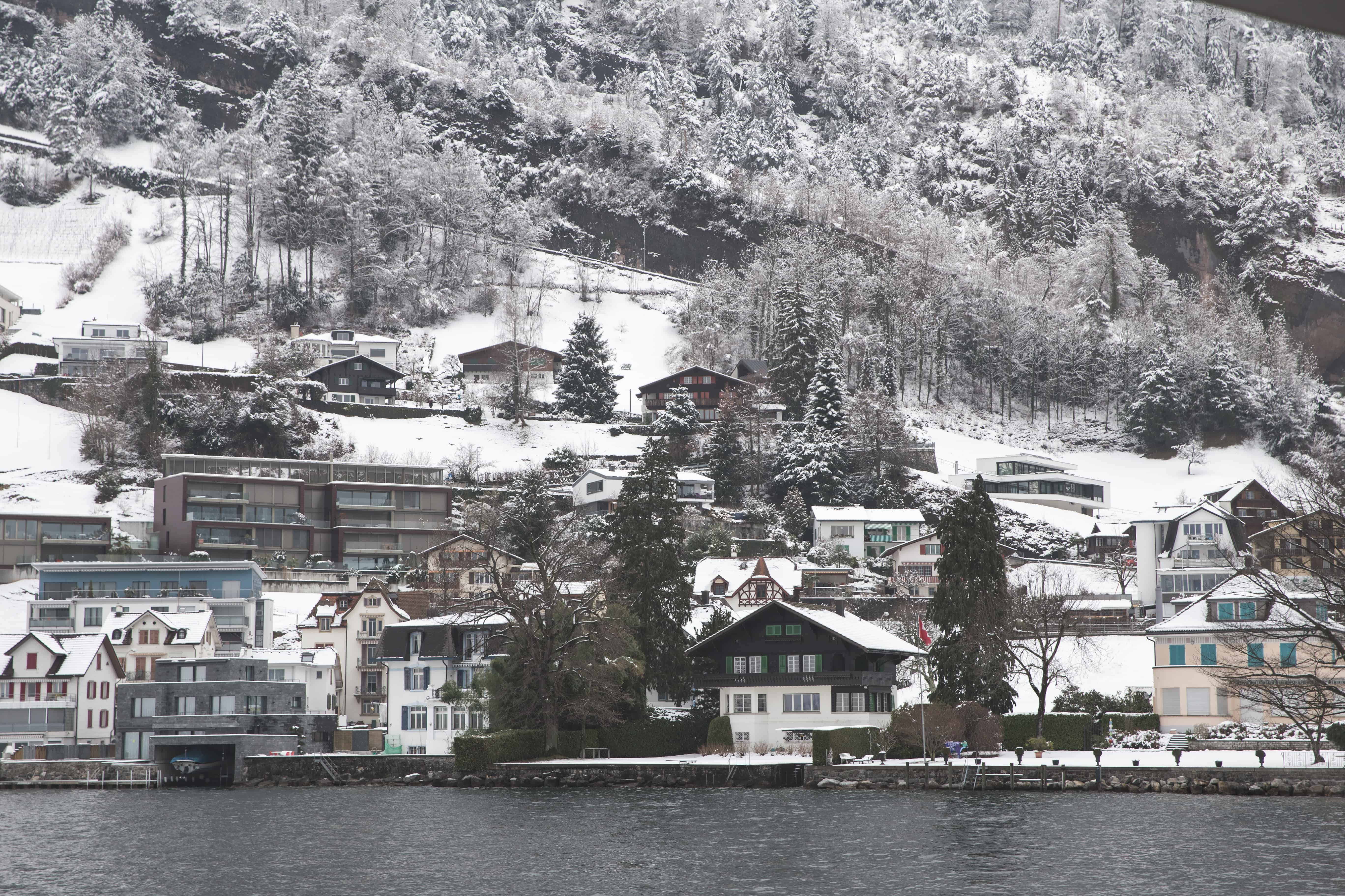 Lake houses in February are covered in snow on Lake Lucerne in Switzerland