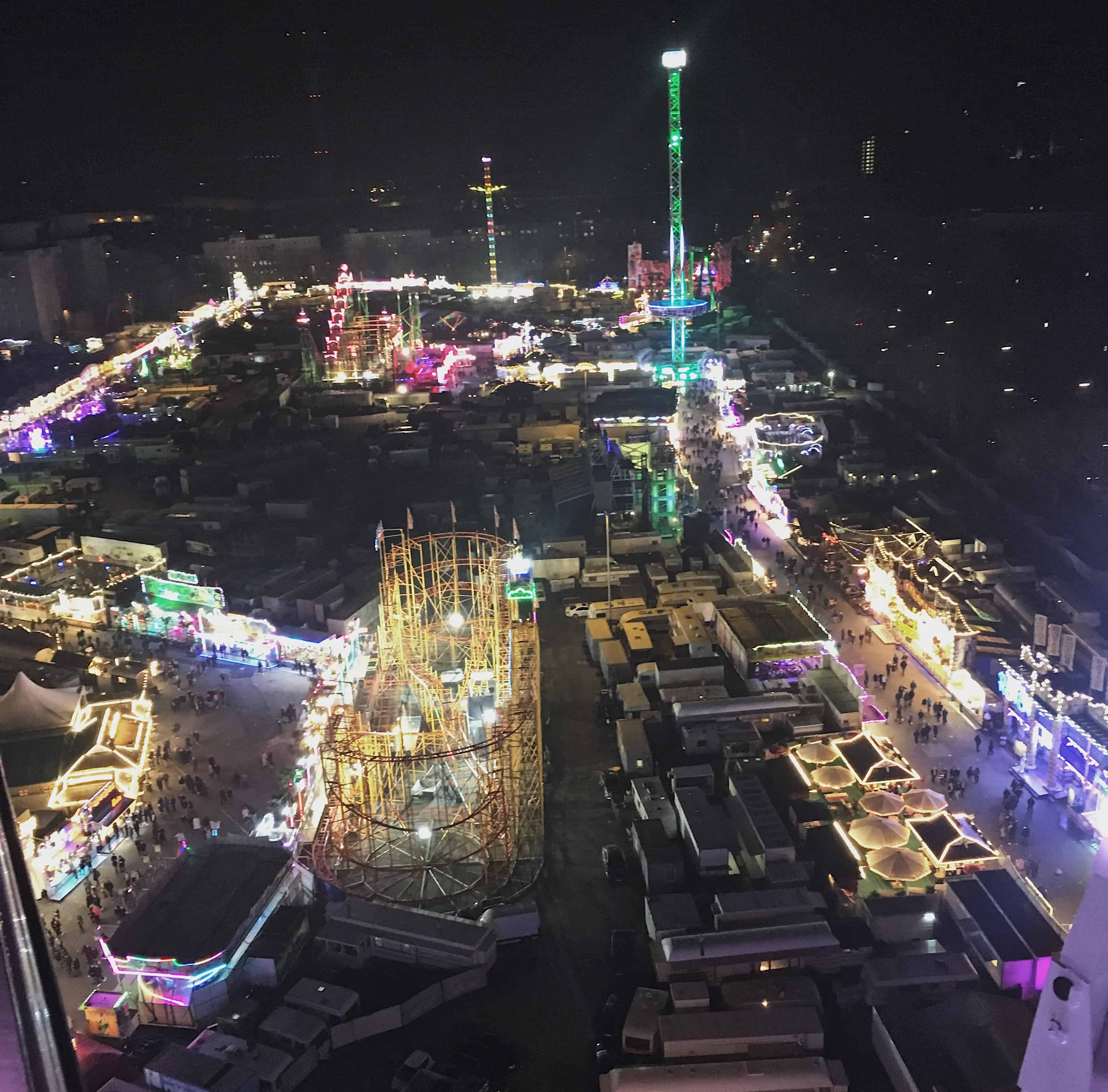 View of the brightly lit Hamburger DOM Carnival from the ferris wheel at night in Hamburg, Germany