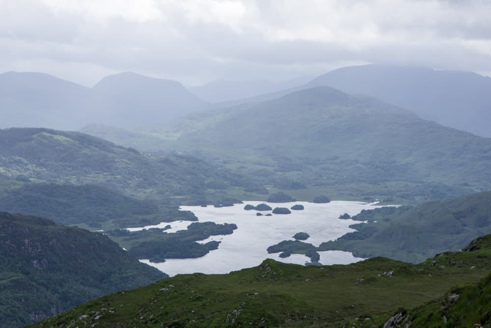 The hike up to Torq Mountain in Killarney National Park in Ireland - a view of a cloudy sky, mountains, and a lake