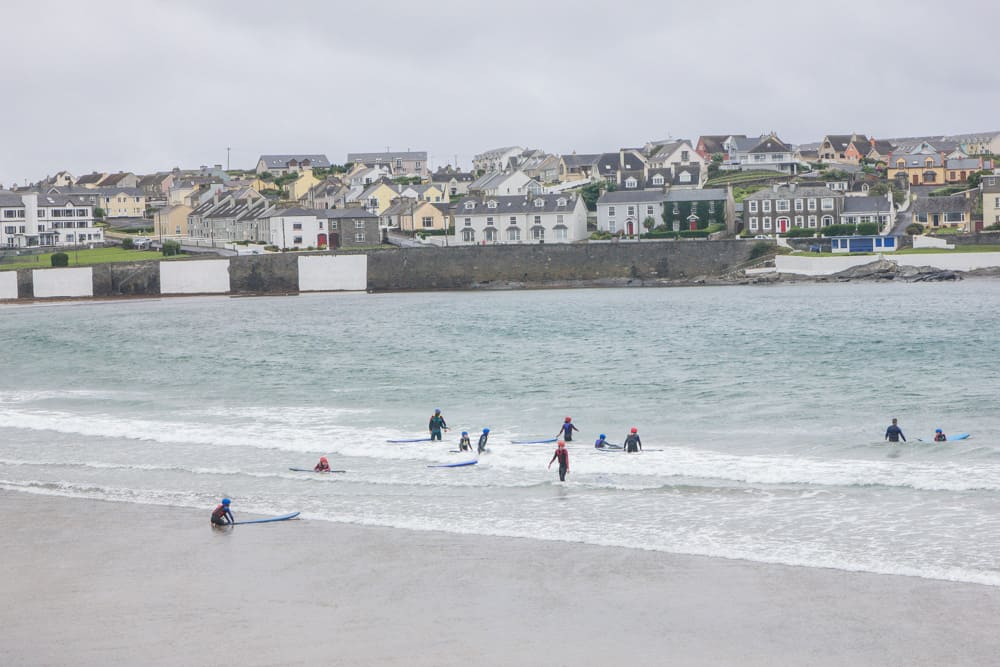 Surfers and swimmers in a beach in Kilkee in Ireland