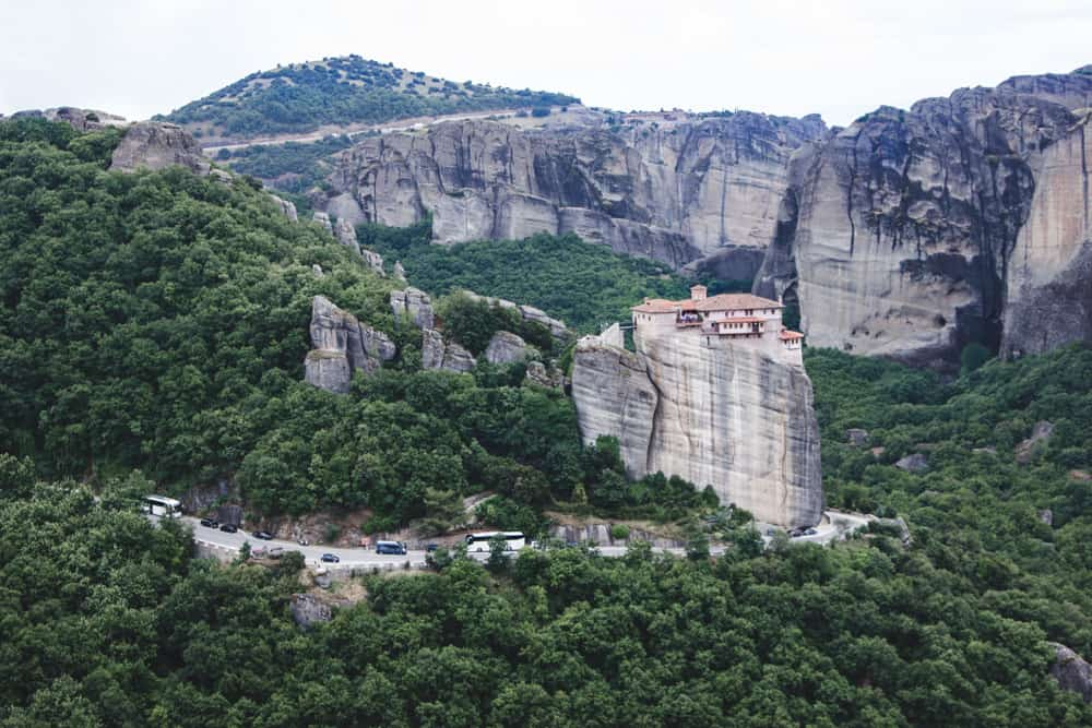 Monastery on a cliff above a road and trees at Meteora in Greece