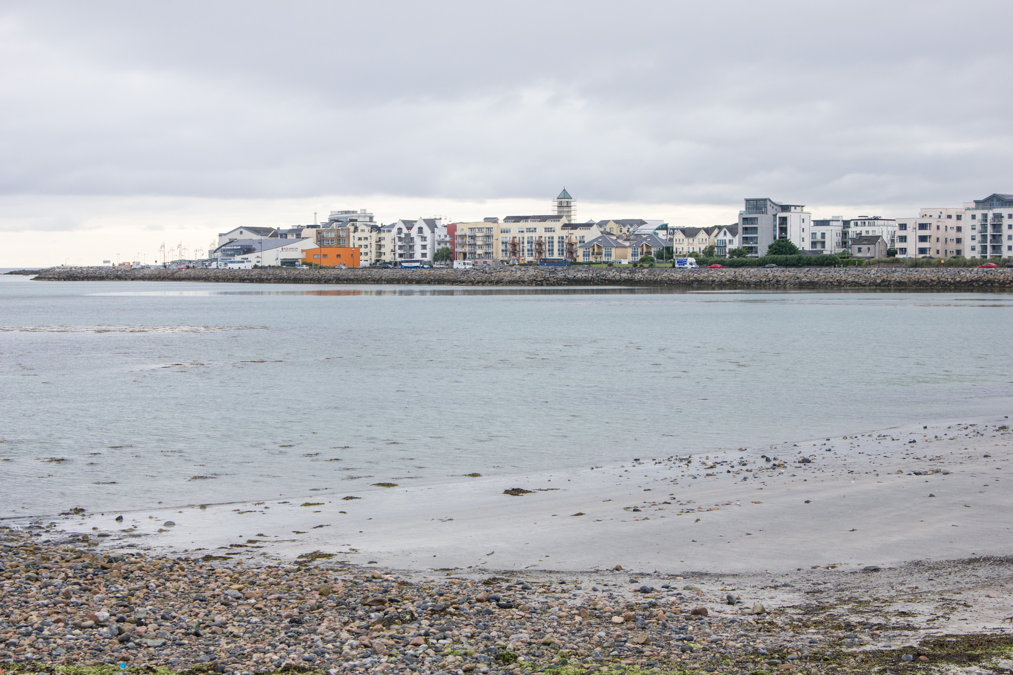 Salthill Promenade Walk in Galway, Ireland is along the coast with views of the ocean and houses behind it