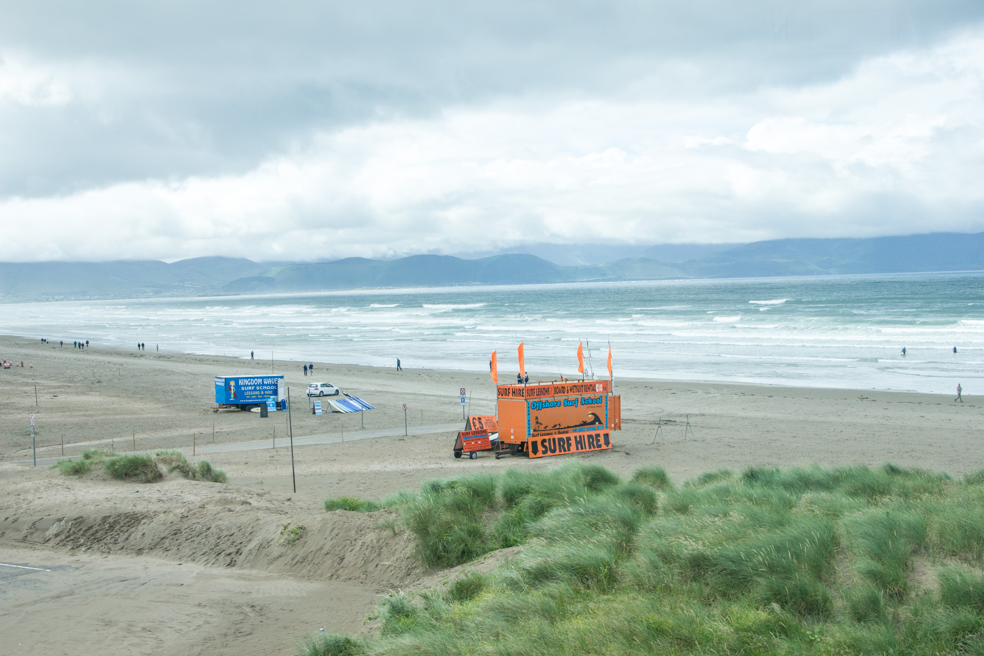 Beach in Dingle, Ireland with an orange truck on the shore