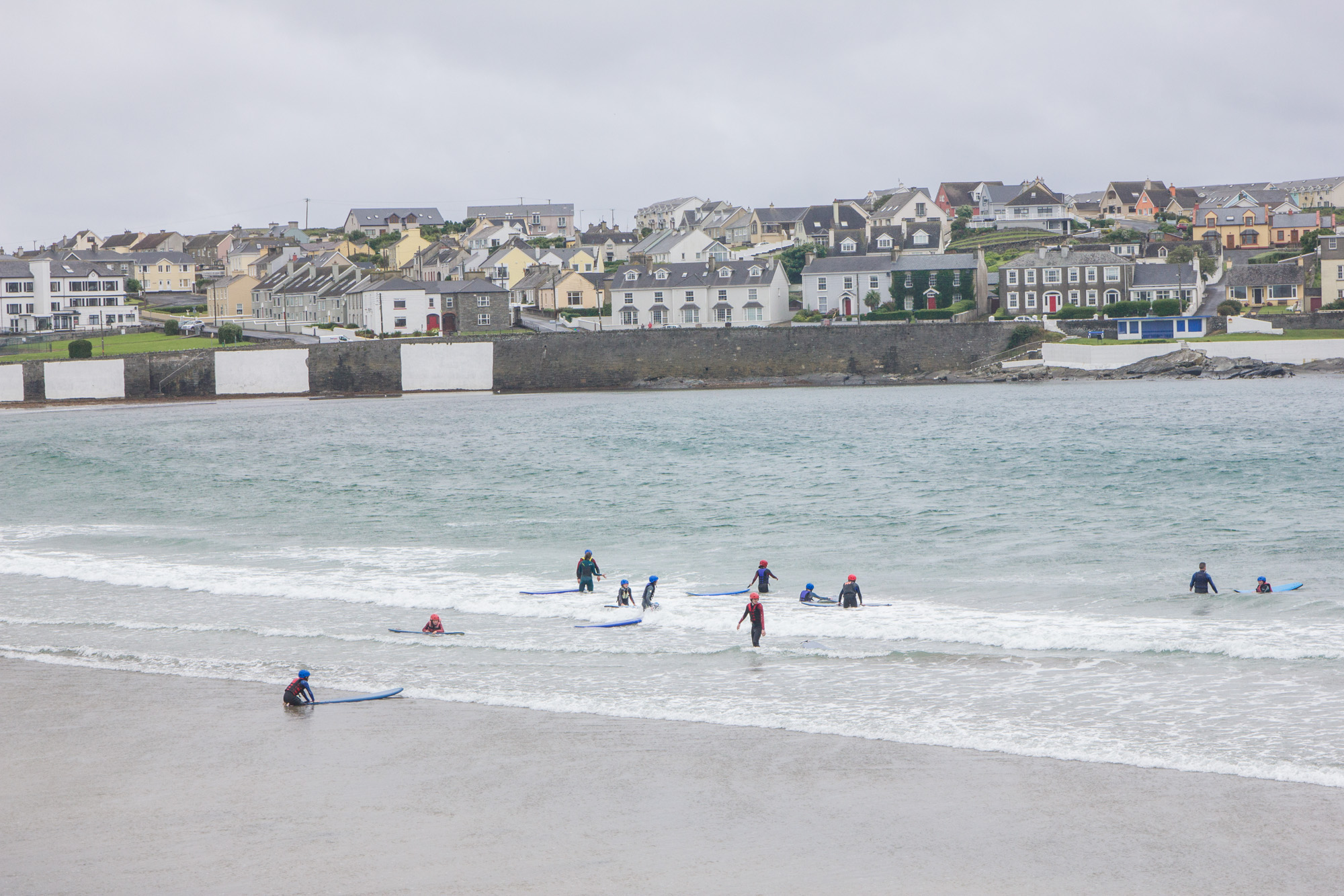 Beach in Kilkee, Ireland full of surfers with a view of the town behind it
