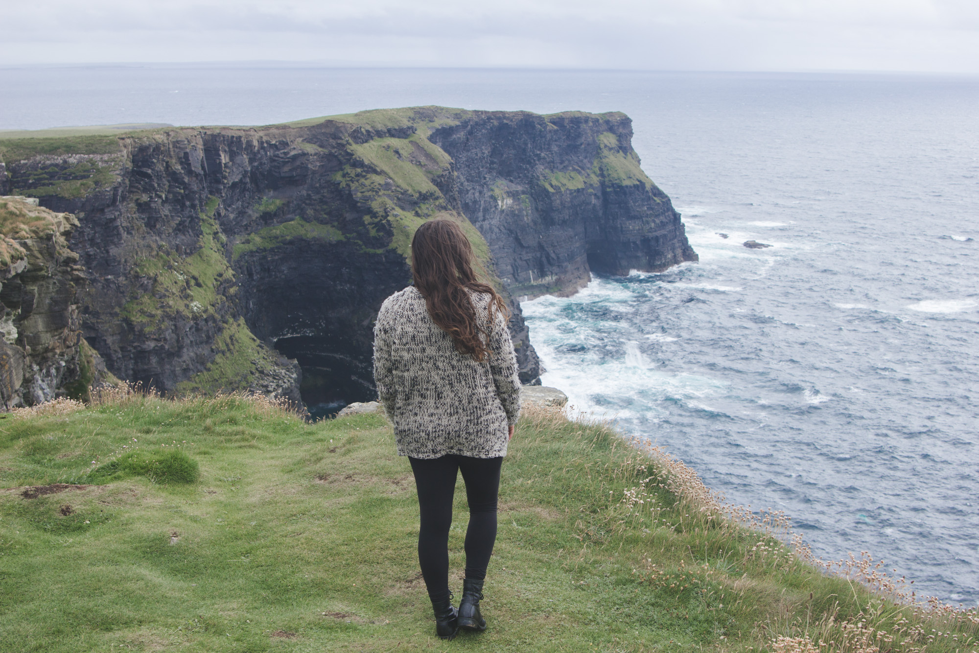 Kelsey standing on Hag's Head near the Cliffs of Moher in Ireland