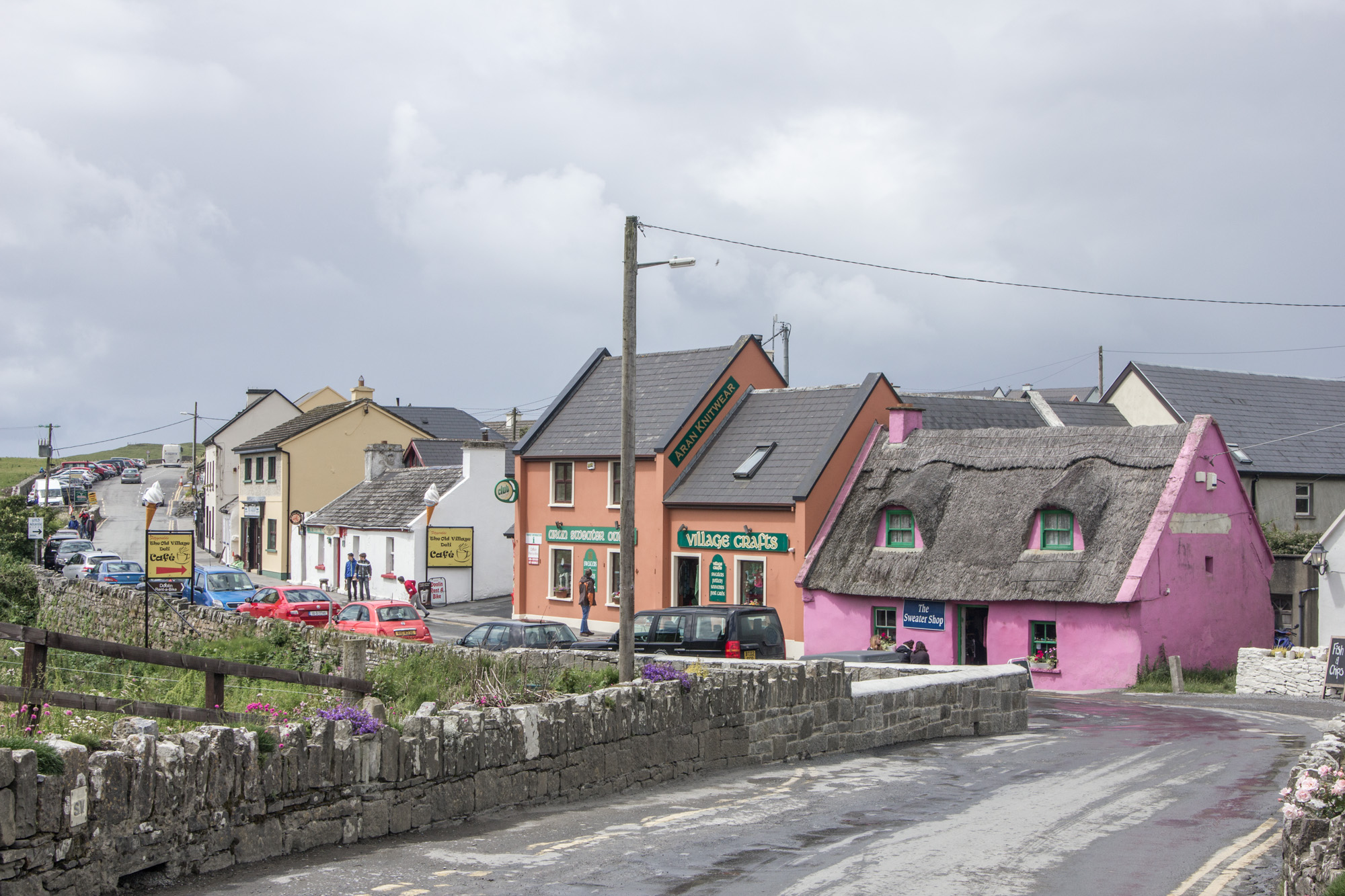 The main street in Doolin, Ireland has a pink, orange, and white buildings