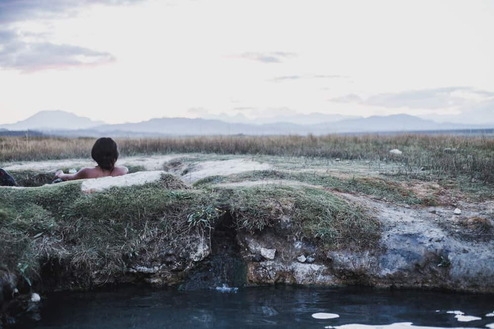 Girl in Wild Willy's Hot Springs in Mammoth California surrounded by grassland and mountains at sunset