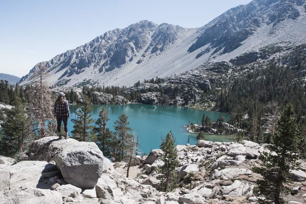 Woman standing on rock looking at First Lake (bright blue water surrounded by trees and rocky mountains) in Big Pine Lakes, California
