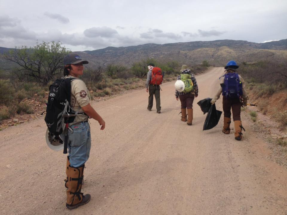 4 conservation corps members walking in the desert in Arizona