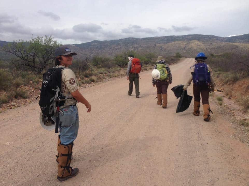 4 people on dirt road in Saguaro National Park in the Arizona desert after a long day working in the conservation corps