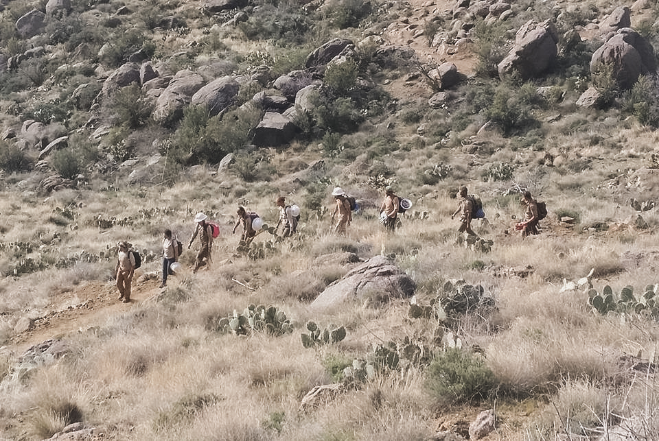 9 Conservation corps members hiking down a mountain after a day spent trail building in Yarnell, Arizona